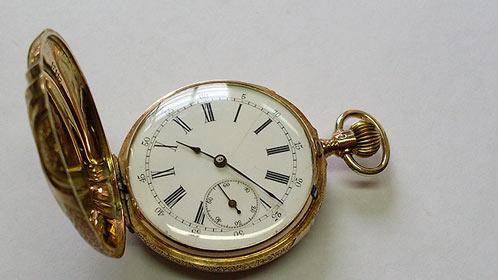 Pohled na číselník zlatých kapesních hodinek po renovaci